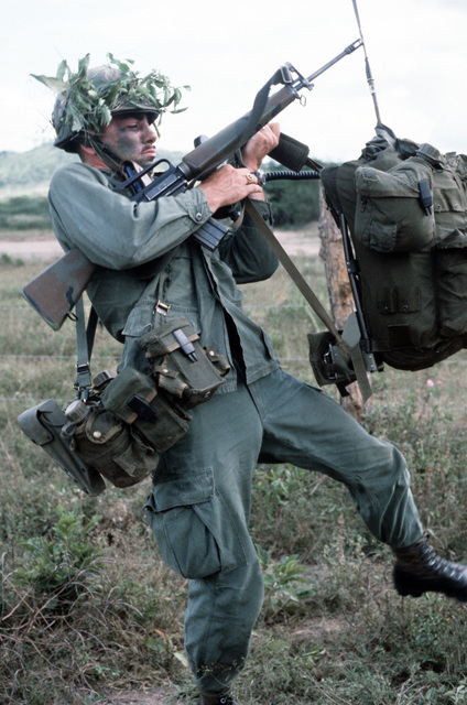 A radioman from Company B, 1ST Battalion, 187th Infantry, 193rd Brigade Task Force from Panama, attempts to put on his back pack while holding an M16A1 rifle, during the joint US/Honduras training Exercise AHUAS TARA II (BIG PINE)