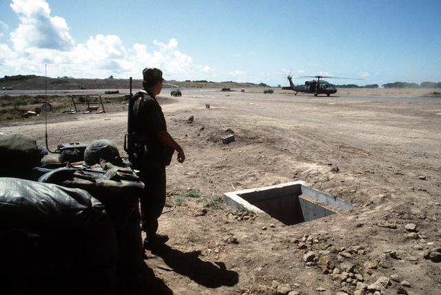 A US Air Force security policeman stands guard near the runway at Point Salines Airport during Operation URGENT FURY. The UH-60 Black Hawk (Blackhawk) helicopter in the background is carrying General Thomas M. Ryan Jr., commander in chief, Military Airlift Command (MAC), who has just completed a tour of the island