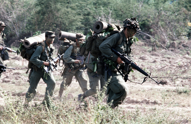 Members of Company B, 1ST Battalion, 187th Infantry, 193rd Brigade Task Force from Panama, move out across a field during the joint US/Honduras training Exercise AHUAS TARA II (BIG PINE). They are wearing camouflage and are armed with M16A1 rifles