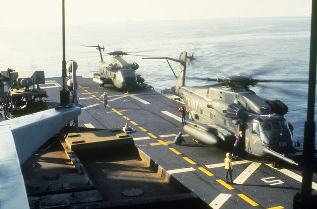 A CH-53E Super Stallion helicopter (foreground) and a CH-53 Sea Stallion helicopter on the flight deck of the amphibious assault ship USS GUAM (LPH-9) during operations off the coast of Beirut, Lebanon