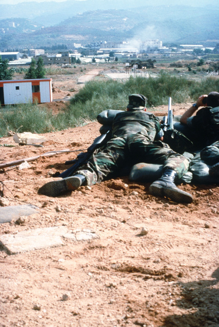 Marines at an observation/sniper post of Company B, 1ST Battalion, 8th Regiment, 24th Marine Amphibious Unit, scan hostile positions for the source of incoming fire