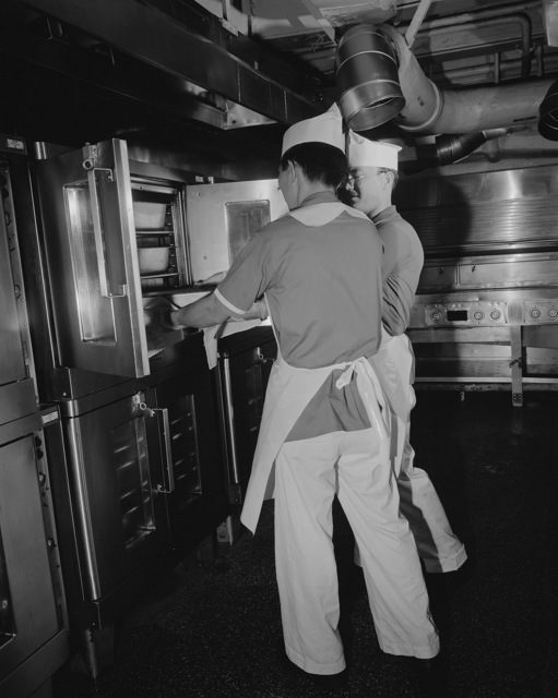 Mess management specialists pull a pan of food from an oven in the galley aboard the nuclear-powered aircraft carrier USS ENTERPRISE (CVN 65)
