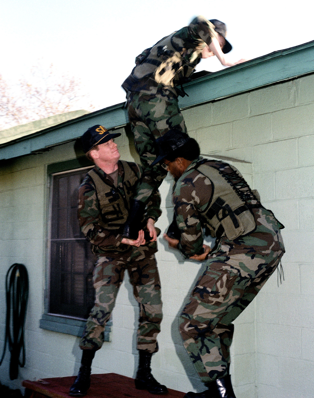 Private First Class Ernest J. Williams is boosted onto a roof by SPECIALIST, Fouth Class Howard Griffin and STAFF Sergeant James A. Jordan during a security exercise...The men are members of the Special Reaction Team (SRT)