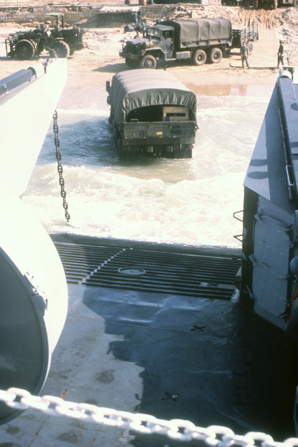 A cargo truck is driven off a utility landing craft by a Marine beachmaster during a multinational peacekeeping operation