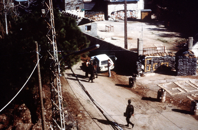 A view from atop Checkpoint 76 as a Marine inspects a vehicle during a multinational peacekeeping operation