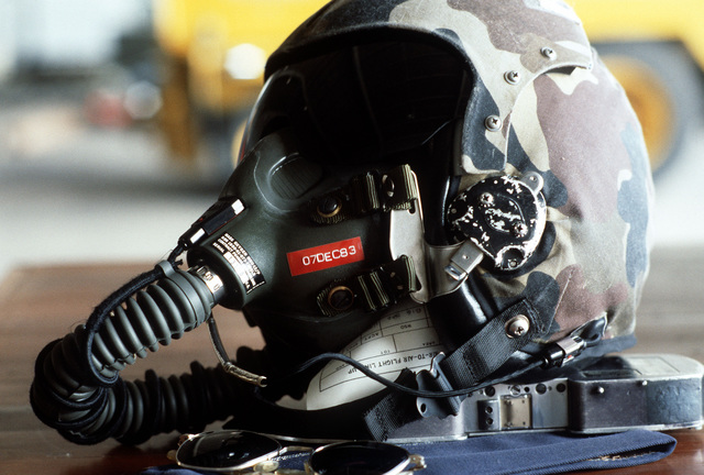 A flight helmet, oxygen mask, gun film cassette, and flight glasses belonging to a US Air Force photographer. The equipment will be used during aerial photography for the dissimilar aircraft flying Exercise COMMANDO WEST 6. Third Tactical Fighter Squadron personnel and aircraft will participate in the exercise with members of the Royal Thai Air Force