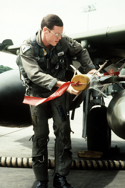 First Lieutenant Rick Scarbrook, 3rd Tactical Fighter Squadron, inspects a Sidewinder (AIM-9) missile during a preflight check of his F-4 Phantom II aircraft. He is preparing for a flight to Takhli Royal Thai Air Force Base, Thailand, where he will participate in the dissimilar aircraft flying Exercise COMMANDO WEST 6 with members of the Royal Thai Air Force