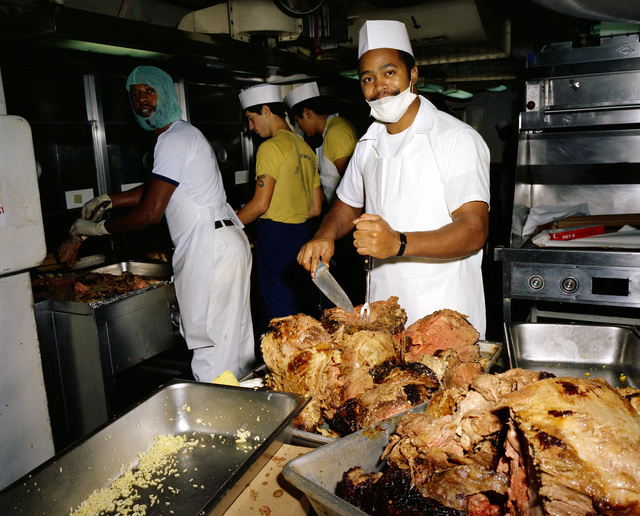 Mess management specialists prepare a meal for the 22nd anniversary of the nuclear-powered aircraft carrier USS ENTERPRISE (CVN 65) in the galley of the ship