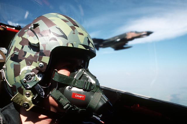 Technical Sergeant David N. Craft, a US Air Force photographer, in the cockpit of an aircraft during the dissimilar aircraft flying Exercise COMMANDO WEST 6. Personnel and aircraft of the 3rd Tactical Fighter Squadron are participating in the exercise with members of the Royal Thai Air Force. A 3rd TFS F-4 Phantom II aircraft is visible through the canopy