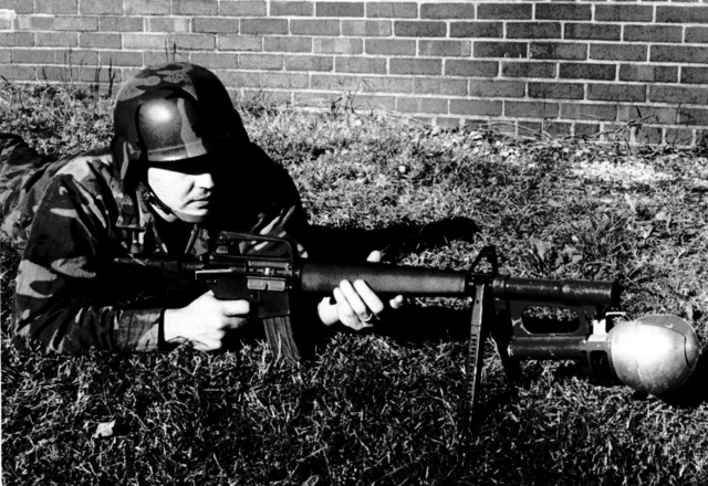 A Marine prepares to launch a Rifleman's Assault Weapon (RAW) attached to the muzzle of an M16 rifle