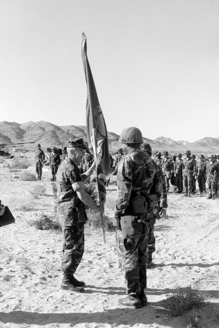 Brigadier General William R. Etnyre (left), commanding general of the combat center and the 7th Marine Amphibious Brigade, retires the colors of the 3rd Battery, 4th Bn., 11th Marines, 1ST Marine Division, during their last formation as an M107 175 mm self-propelled howitzer unit. Their M107s (background) will be retired and the battery will convert to 8-inch howitzers