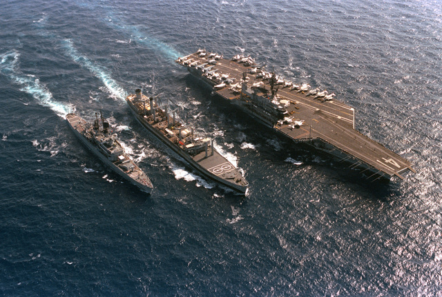 A starboard bow view of the oiler USNS NAVASOTA (T-AO 106) conducting an underway replenishment of the aircraft carrier USS MIDWAY (CV 41) off the port side and the guided missile cruiser USS ENGLAND (CG 22) off the starboard side