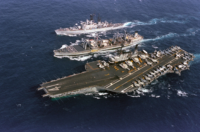 An elevated port bow view of the oiler USNS NAVASOTA (T-AO 106) conducting an underway replenishment of the aircraft carrier USS MIDWAY (CV 41) off its port side and the guided missile cruiser USS ENGLAND (CG 22) off its starboard side