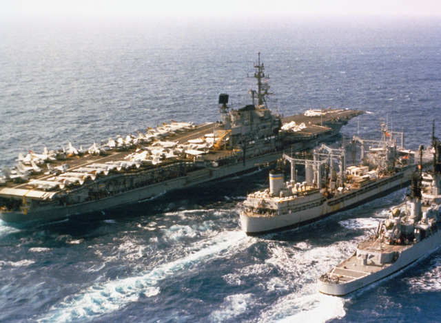 An elevated starboard quarter view of the oiler USNS NAVASOTA (T-AO 106) conducting an underway replenishment of the aircraft carrier USS MIDWAY (CV 41) off port and the guided missile cruiser USS ENGLAND (CG 22) off starboard