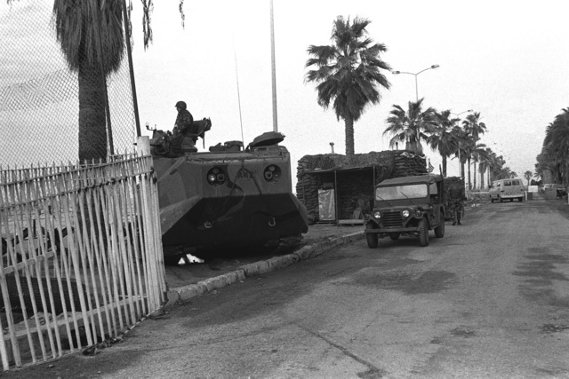 An LTVP 7 armored amphibious assault vehicle is used to block a road leading into the US Embassy compound, as Marines take special security measures during a multinational peacekeeping operation