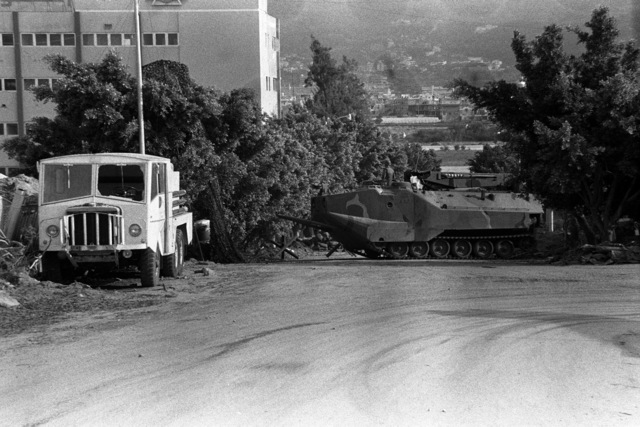 An LVTP 7 armored amphibious assault vehicle is used to block a road leading into a vital area of operation for Marines of the 22nd Marine Amphibious Unit, as they participate in a multinational peacekeeping operation