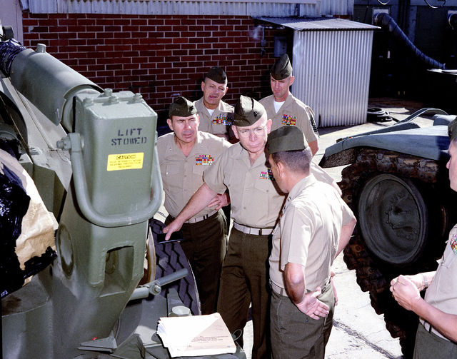 Captain P. J. Folicoeur, right, special projects officer, Repair Division, explains the function of an M198 artillery piece to General P. X. Kelly, center, Commandant of the Marine Corps. Looking on from left to right are, Major General R. A. Shaffer, Sergeant Major (SGM) R. E. Cleary and SGM R. E. Behrend