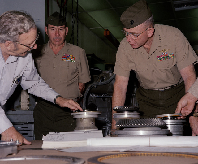 W. P. Miller, left, foreman, Power Crane Shop, Repair Division, explains a portion of the landing vehicle, tracked (LVT7) transmission to General P. X. Kelly, Commandant of the Marines Corps. Looking on is Major General R. A. Shaffer, center, Commanding General, Marine Corps Logistics Base