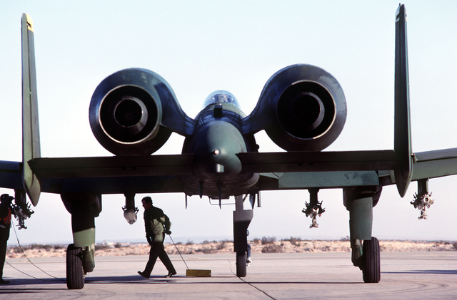 A rear view of an A-10 Thunderbolt II aircraft. The wheel chock is being removed as the plane prepares for takeoff