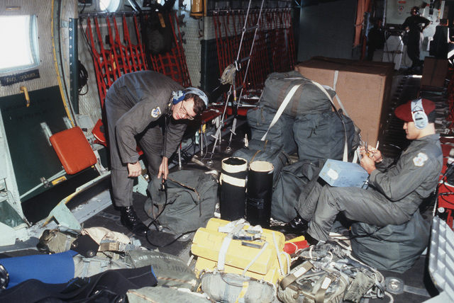 Pararescue specialists STAFF Sergeant John Heath, right, and AIRMAN First Class Jerry Sowles prepare their gear prior to their jump from an HC-130 Hercules aircraft during SAREX '83, a search and rescue training exercise