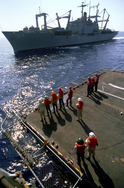 The amphibious cargo ship USS EL PASO (LKA 117) pulls alongside the amphibious assault ship USS IWO JIMA (LPH 2). When the EL PASO is in position, the crewmen on the aircraft elevator of the IWO JIMA will fire shot lines to the cargo ship to begin underway replenishment. The ships are supporting United States Marine and Navy units of the multinational peacekeeping force