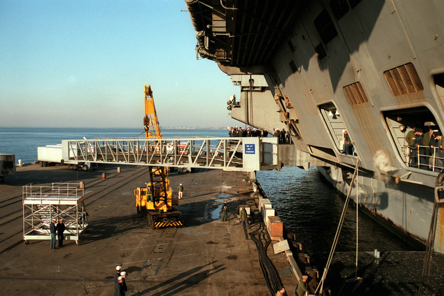 A crane moves a gangway into place on the side of the nuclear-powered aircraft carrier USS DWIGHT D. EISENHOWER (CVN-69) upon its return from a Mediterranean deployment