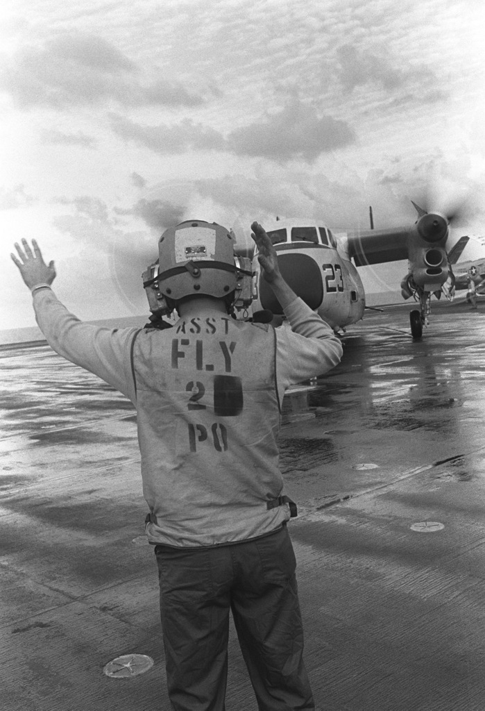 A flight deck crewman signals to the pilot of a C-2 Greyhound aircraft after landing aboard the aircraft carrier USS JOHN F. KENNEDY (CV 67). The C-2 aircraft is being used to transport the body of Lieutenant (LT) Mark Adam Lange back to the US. LT Lange was killed when his A-6 aircraft was shot down during a bombing raid over Lebanon