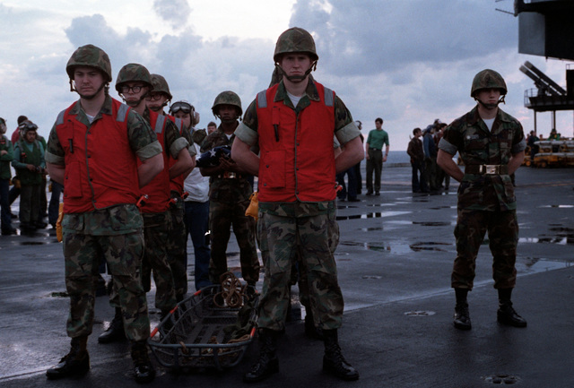A Marine casket team stands by on the flight deck of the aircraft carrier USS JOHN F. KENNEDY (CV 67) to remove the casket of Lieutenant (LT) Mark Adam Lange from a CH-46 Sea Knight helicopter. LT Lange was killed when his A-6 aircraft was shot down in a bombing raid over Lebanon