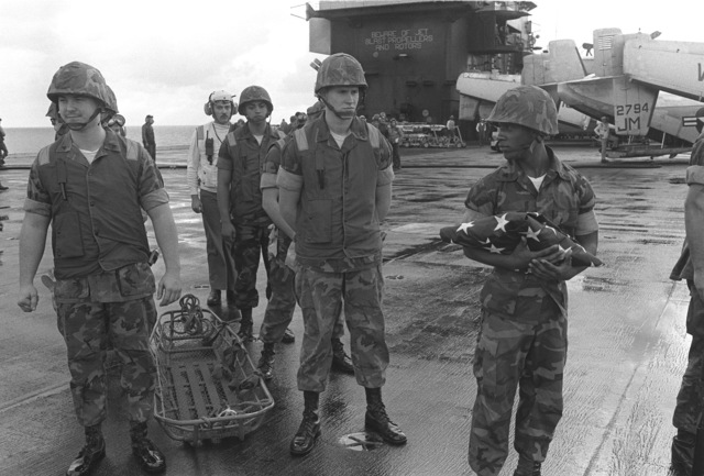 A Marine flag bearer and casket team stand by on the flight deck of the aircraft carrier USS JOHN F. KENNEDY (CV 67), to remove the casket of Lieutenant (LT) Mark Adam Lange from a CH-46 Sea Knight helicopter. LT Lange was killed when his A-6 aircraft was shot down during a bombing raid over Lebanon