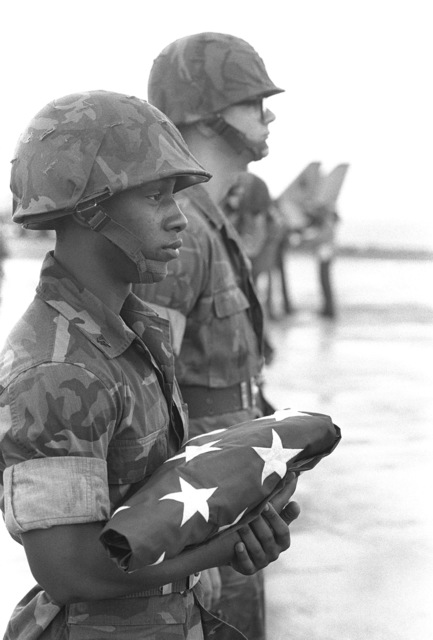 A Marine flag bearer stands on the flight deck of the aircraft carrier USS JOHN F. KENNEDY (CV 67), awaiting the arrival a CH-46 Sea Knight helicopter carrying the body of Lieutenant (LT) Mark Adam Lange. LT Lange was killed when his A-6 aircraft was shot down during a bombing raid over Lebanon