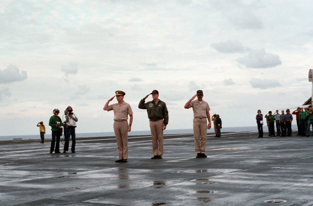 From left to right, Rear Admiral Roger E. Cox, Commander, Carrier Group Six; Captain (CAPT) Gary F. Wheatley, commanding officer of the USS JOHN F. KENNEDY (CV 67); and CAPT John A. Pieno, the ship's executive officer, salute as the body of Lieutenant (LT) Mark Adam Lange arrives aboard the aircraft carrier. LT Lange was killed when his A-6 Intruder aircraft was shot down over Lebanon