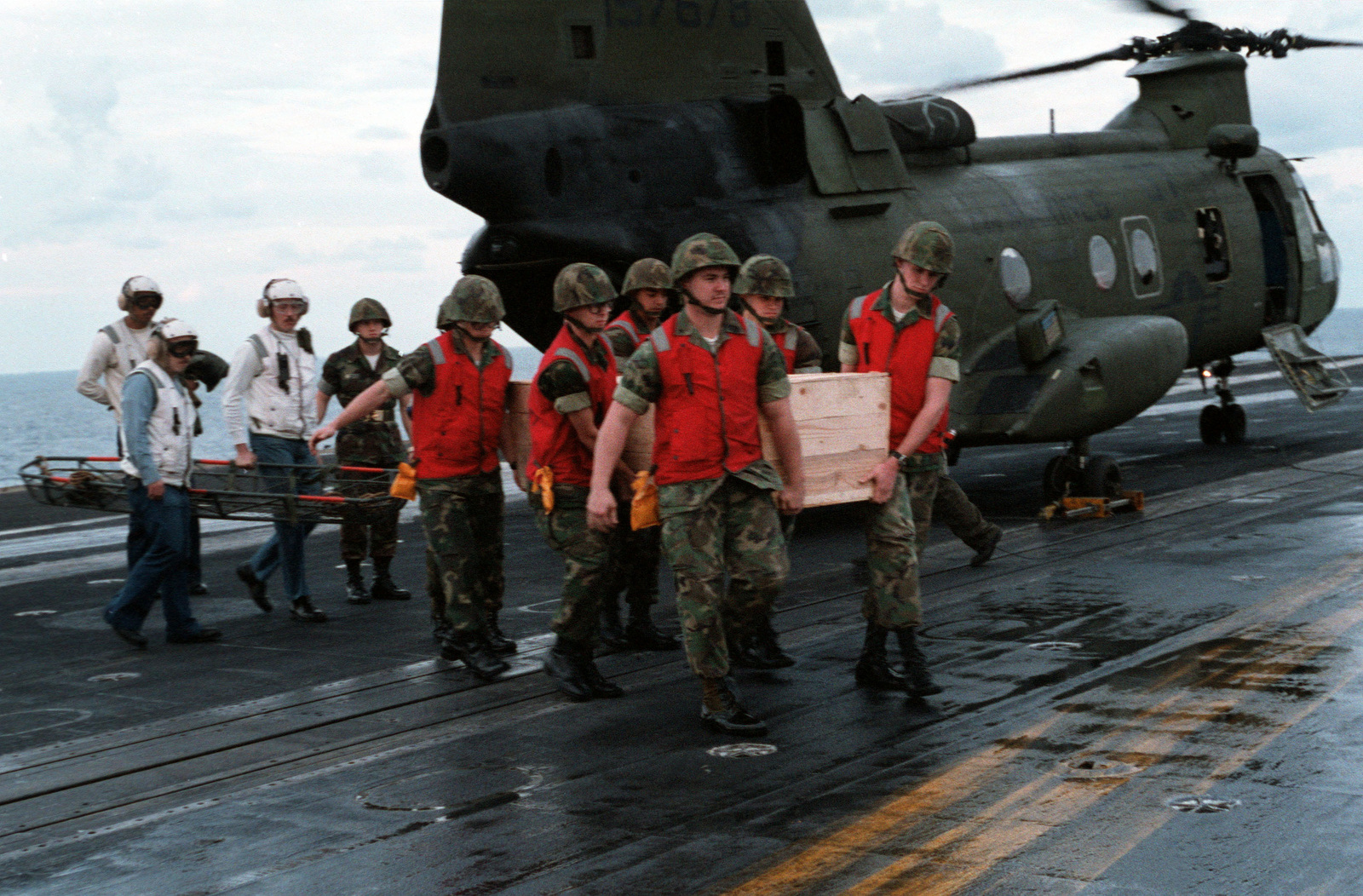 Marines carry a box containing the body of Lieutenant (LT) Mark Adam Lange from a CH-46 Sea Knight helicopter after its arrival aboard the aircraft carrier USS JOHN F. KENNEDY (CV 67). LT Lange was killed when his A-6 Intruder aircraft was shot down in a bombing raid over Lebanon