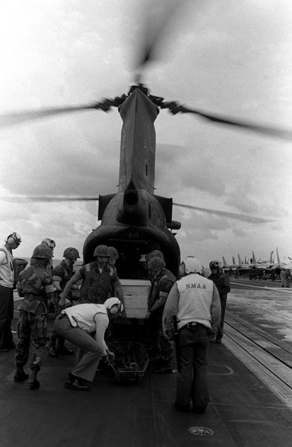 Marines carry the casket of LT. Mark Adam Lange from a CH-46 Sea Knight helicopter after its arrival aboard the aircraft carrier USS JOHN F. KENNEDY (CV-67). LT. Lange was killed when his A-6 aircraft was shot down during a bombing raid over Lebanon