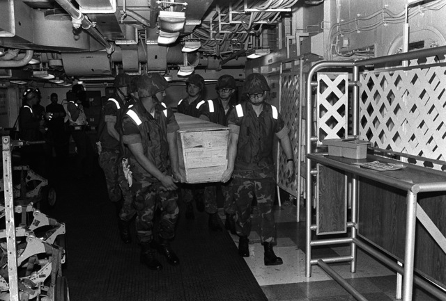 Marines carry the casket of LT. Mark Adam Lange to the dispensary aboard the aircraft carrier USS JOHN F. KENNEDY (CV-67) for identification and examination of the body. LT. Lange was killed when his A-6 aircraft was shot down during a bombing raid over Lebanon