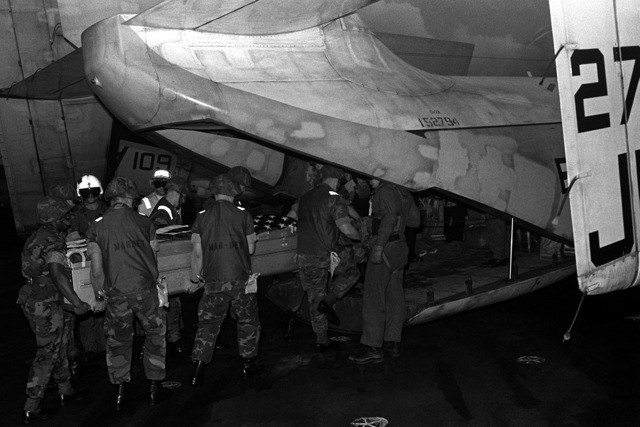 Marines carry the flag-draped casket of LT. Mark Adam Lange aboard a C-2 Greyhound aircraft for transport from the aircraft carrier USS JOHN F. KENNEDY (CV-67). LT. Lange was killed when his A-6 aircraft was shot down during a bombing raid over Lebanon