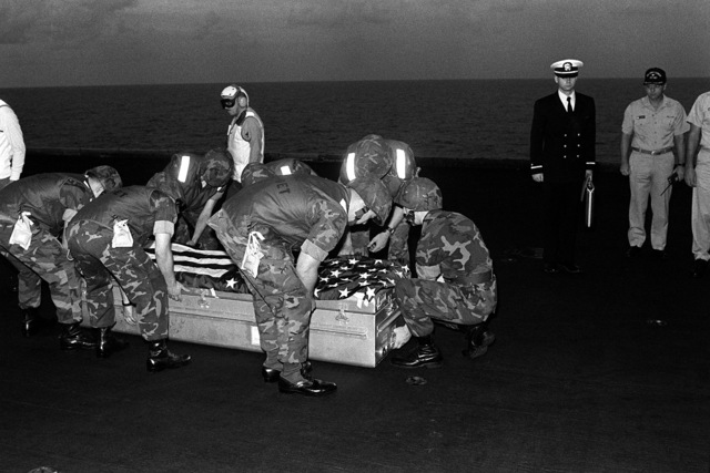 Marines pick up the flag-draped casket of LT. Mark Adam Lange to be placed aboard a C-2 Greyhound aircraft for transport from the aircraft carrier USS JOHN F. KENNEDY (CV-67). LT. Lange was killed when his A-6 aircraft was shot down during a bombing raid over Lebanon