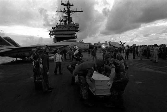 Marines place the casket of LT. Mark Adam Lange onto elevator one aboard the aircraft carrier USS JOHN F. KENNEDY (CV-67), to be taken below for identification and examination of the body. LT. Lange was killed when his A-6 aircraft was shot down during a bombing raid over Lebanon