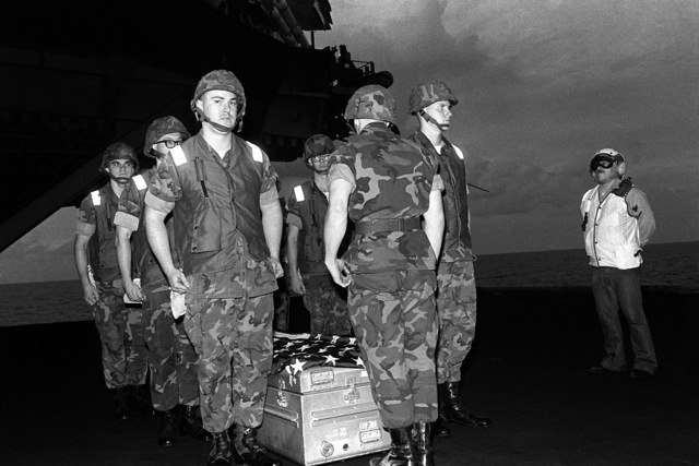 Marines prepare to place the flag-draped casket of LT. Mark Adam Lange aboard a C-2 Greyhound aircraft for transport from the aircraft carrier USS JOHN F. KENNEDY (CV-67). LT. Lange was killed when his A-6 aircraft was shot down during a bombing raid over Lebanon