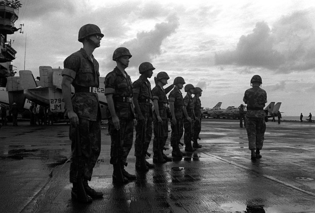 Marines stand at attention on the flight deck of the aircraft carrier USS JOHN F. KENNEDY (CV-67) awaiting the arrival of a CH-46 Sea Knight helicopter carrying the body of LT. Mark Adam Lange. LT. Lange was killed when his A-6 aircraft was shot down in a bombing raid over Lebanon