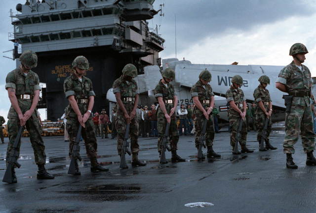 Marines stand in the ceremonial at ease position on the flight deck of the aircraft carrier USS JOHN F. KENNEDY (CV 67), awaiting the arrival of the body of Lieutenant (LT) Mark Adam Lange aboard a CH-46 Sea Knight helicopter. LT Lange was killed when his A-6 aircraft was shot down during a bombing raid over Lebanon