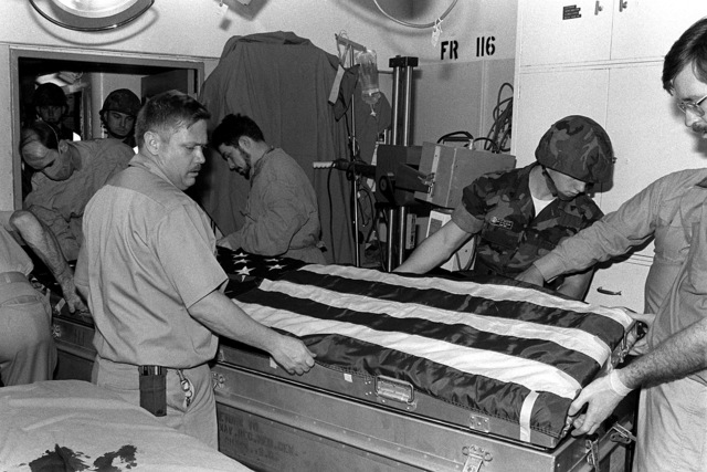 The flag-draped casket of LT. Mark Adam Lange is prepared for transport from the aircraft carrier USS JOHN F. KENNEDY (CV-67) after identification and examination of the body. LT. Lange was killed when his A-6 aircraft was shot down during a bombing raid over Lebanon