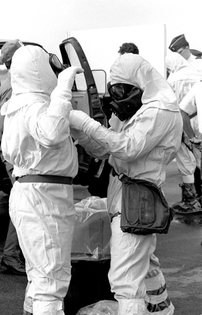 AIRMAN First Class (A1C) Richard Boom of the disaster response force assists A1C Doug Pearsons with his chemical protective outfit during a disaster response exercise. Their outfits are equipped with M17 chemical-biological field masks