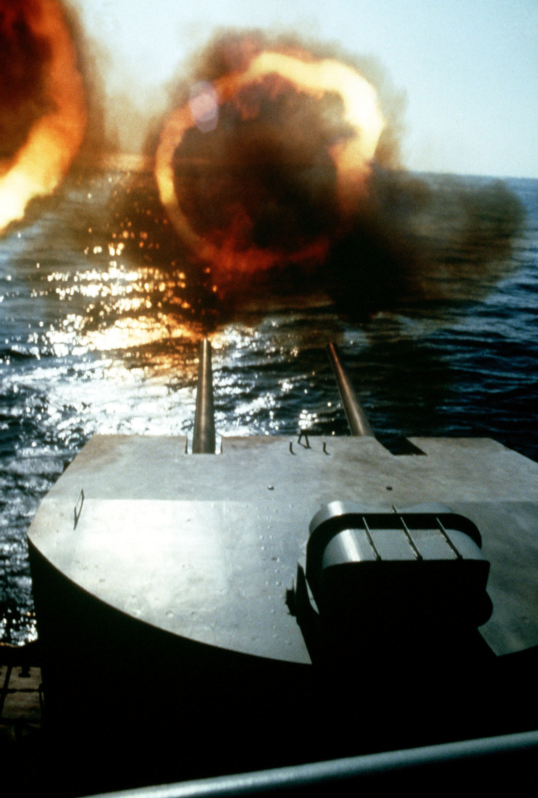 Rings of fire erupt from one of the 5-inch/38-caliber twin gun mounts of the battleship USS NEW JERSEY (BB 62) during a practice firing off the coast of Beirut, Lebanon