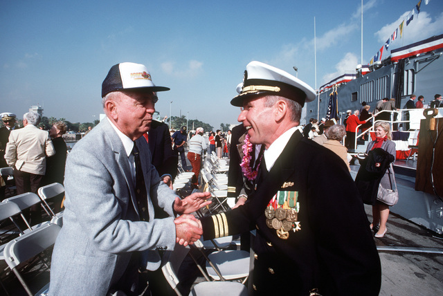 M. L. Leslie is greeted by Commander Robert B. Lynch, prospective commanding officer, during the commissioning ceremony for the guided missile frigate USS MCCLUSKY (FFG 41). Leslie fought at the battle of Midway with the ship's namesake, Rear Admiral Clarence W. McClusky