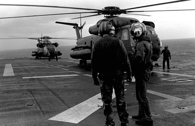 Two crewmen discuss their duties on the flight deck of the amphibious assault ship USS GUAM (LPH 9), as two CH-53 Sea Stallion helicopters are prepared for takeoff during operations off the coast of Beirut, Lebanon