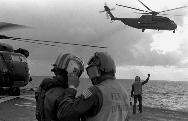 Two crewmen discuss their duties on the flight deck of the amphibious assault ship USS GUAM (LPH 9), as a CH-53 Sea Stallion helicopter takes off during operations off the coast of Beirut, Lebanon
