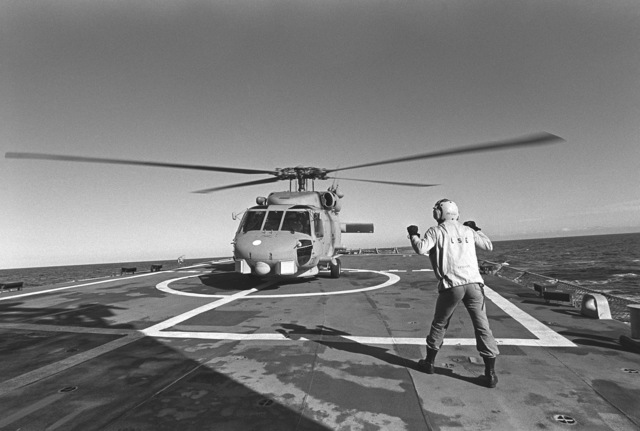 A plane director signals instructions to the pilot of the Navy's first operational Mark III LAMPS (Light Airborne Multi-Purpose System) SH-60B Seahawk helicopter. The helicopter is undergoing flight deck landing qualifications aboard the guided missile frigate USS CROMMELIN (FFG 37), off the coast of San Clemente, California