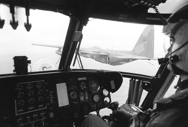 A view looking out the cockpit of a CH-53E Sea Stallion helicopter during refueling operations with a KC-130 Hercules aircraft