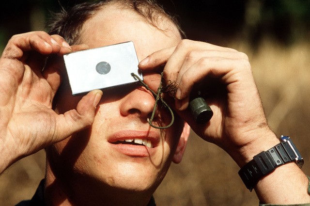 """A """"survivor"""" uses a signal mirror to signal rescuers during Exercise JUNGLE THUNDER"""