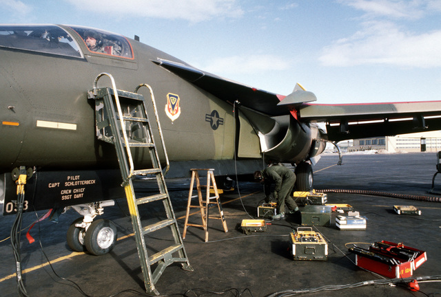 Sergeant James Tate, in cockpit, and SENIOR AIRMAN Mike Stange, both auto-pilot instrumentation specialists, service an F-111A aircraft during maintenance operations on the flight line